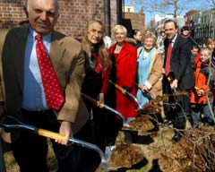 Commissioner Benepe  and other officials plant tree outside library.